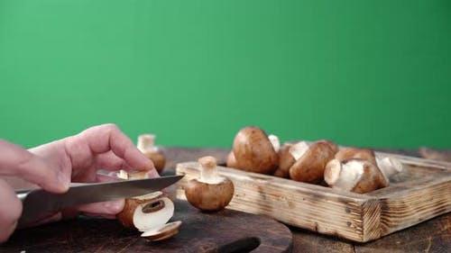 Men Hands Cut Mushrooms with a Knife on a Cutting Board.