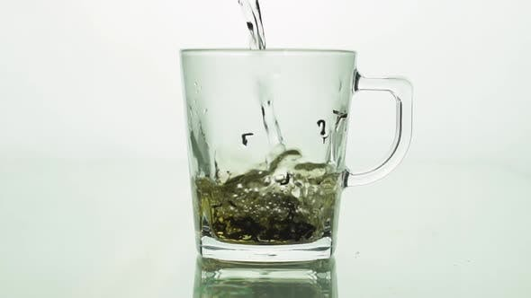 Black Tea Particles Pouring Into Glass Transparent Mug and Filled with Boiling Water To Brew Tea