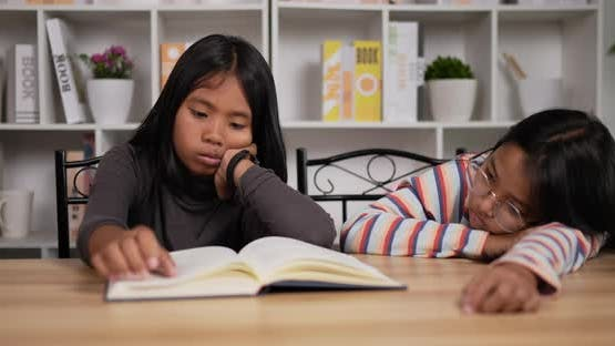 Two bored girls reading a book