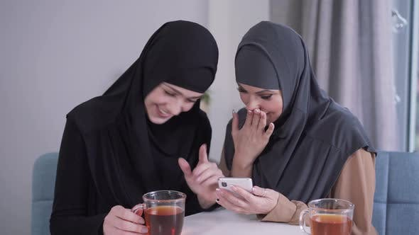 Thumbnail for Modern-looking Muslim Woman Showing Smartphone Screen To Modest Friend in Hijab. Two Women Reacting