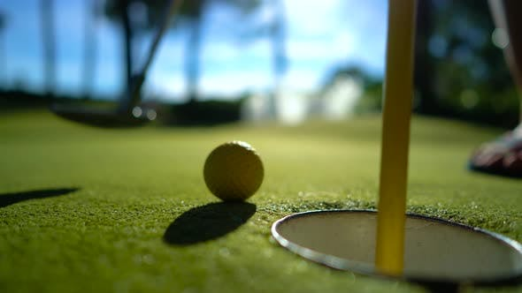 Cover Image for Mini Golf Yellow Ball with a Bat near the Hole at Sunset