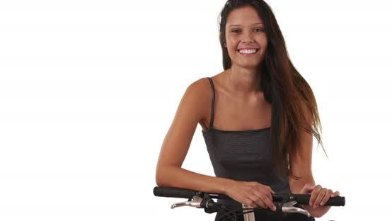 Pretty brunette female with her bike on white background smiling at camera