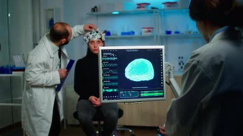 Science Doctor Looking at Computer with Medical Brain Scan Film