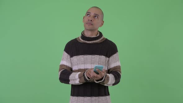 Thumbnail for Happy Bald Multi Ethnic Man Thinking While Using Phone Ready for Winter