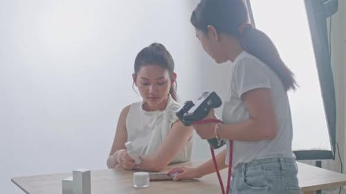Young Asian Female Photographer Explain How To Pose To The Asian Model In Studio