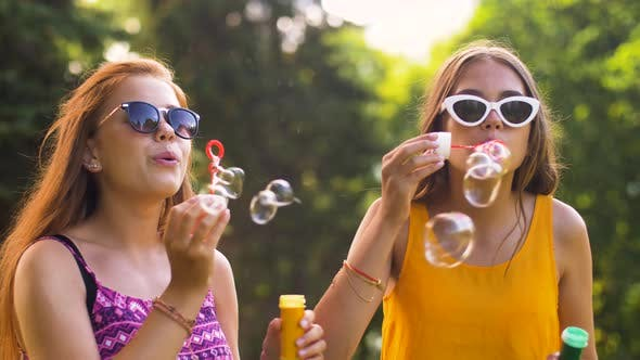 Teenage Girls Blowing Bubbles in Summer Park