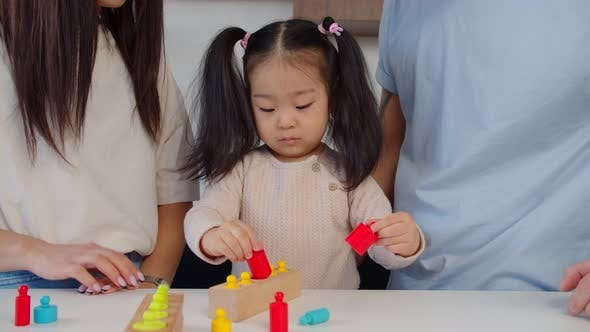 Asian Preschool Age Girl Playing with Educational Toy