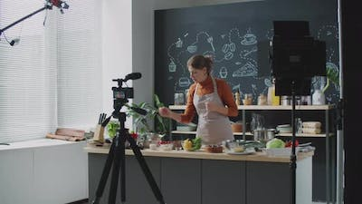 Young Woman Recording Culinary Vlog in Kitchen