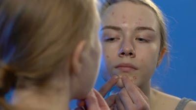 Female Teenager Squeezing Acne