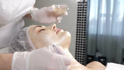 Beauty-Konzept. Kosmetikerin Anwendung Kosmetik Goldene Maske auf schöne weibliche Gesichtshaut. Gesichtsmasken