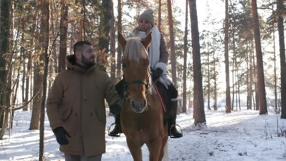 Cover Image for Woman Riding Horse and Talking with Boyfriend in Winter Forest