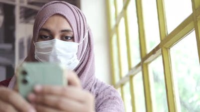 Muslim Women in Face Mask Holding Smart Phone Indoor