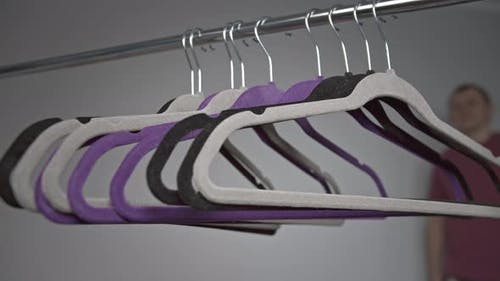 Clothes Hangers a Man Removes One Hanger From a Metal Rack
