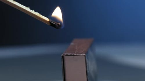 Yellow fire on wooden match goes out above paper box
