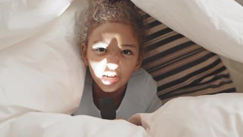 Girl Highlighting Face with Flashlight