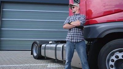 Caucasian Trucker Driver in Front of His Semi Truck