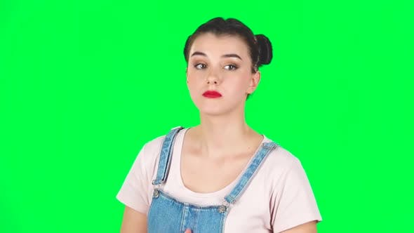 Cover Image for Young Female Stands Waiting with Boredom on Green Screen. Slow Motion