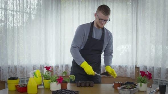 Thumbnail for Male Gardener Planting Vegetables, Pour Soil for Seedlings in Seed Starting Tray