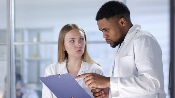 Thumbnail for Male and Female Doctors Discussing Treatment