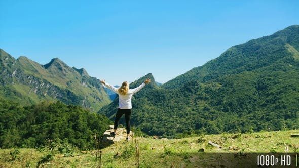 Rear View of Tourist Woman Walking to Mountain Summit with Beautiful Scenic View and Raising Arms