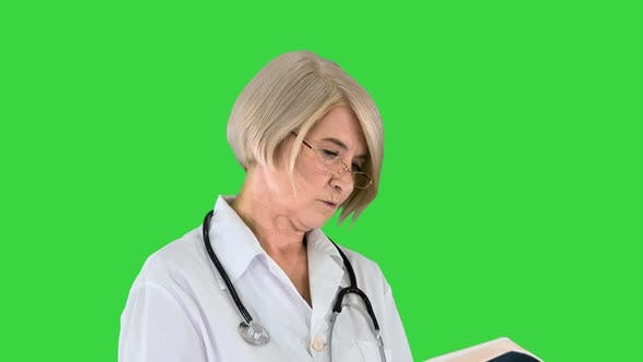 Mature Woman Doctor with a Stethoscope Reading Log on a Green Screen Chroma Key