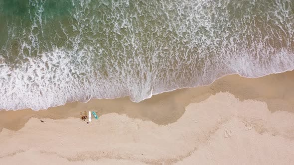 Aerial View of Surf Waves Brushing and Breaking on the White Sandy Seashore on a Summer Day