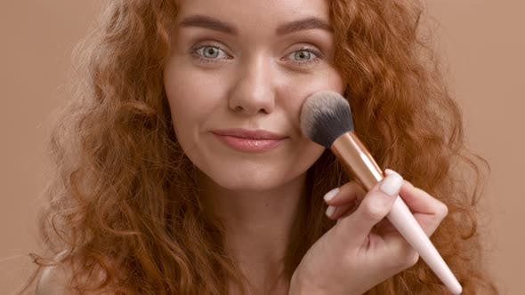Woman Making Makeup Applying Powder With Cosmetic Brush Beige Background