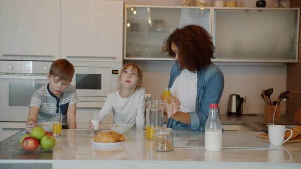 Cheerful Mixed Race Nanny Feeding Caucasian Children with Healthy Breakfast in Kitchen