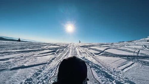 Person Drives Snowmobile Along Empty Track in Snowy Valley