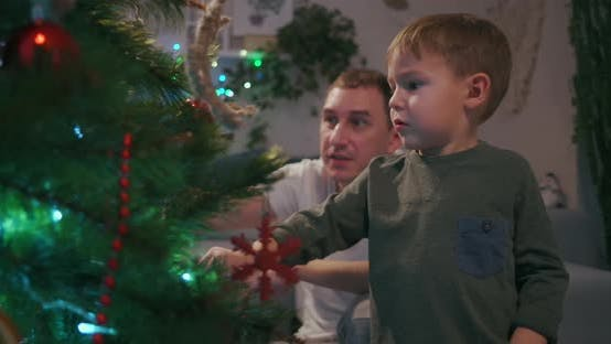 Thumbnail for A Family with Two Children Decorate a Christmas Tree on Christmas Eve