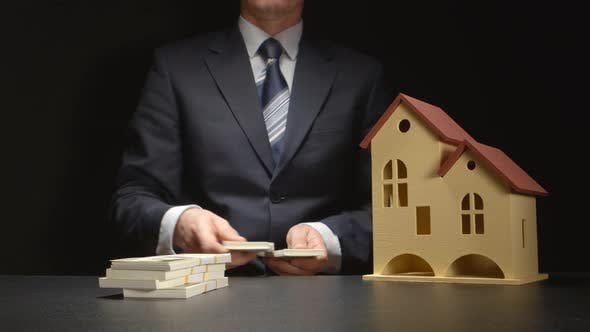 Businessman counts a money and near a house model on a table