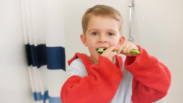 Portrait of Little Boy Cleaning Teeth with Toothbrush Before Going To Sleep at Night