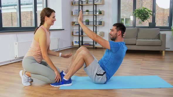 Thumbnail for Man with Personal Trainer Doing Sit Ups at Home