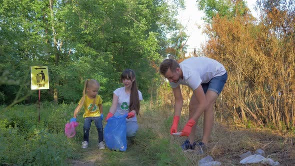 Young Volunteer Male and Female with Child Girl Cares About Ecology Environmental and Collect