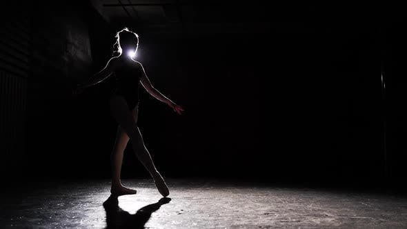 Thumbnail for Professional Flexible Ballerina Dancing on Her Pointe Ballet Shoes in Spotlight on Black Background