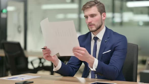 Businessman Reading Documents in Office