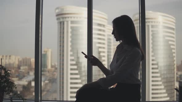 Thumbnail for Silhouette of a Girl with a Phone in Her Hands on the Background of Modern Buildings. Business Woman