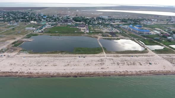 Aerial of Black Sea Sand Spit with Lines of Lounges, Hotels, Houses and Greenery