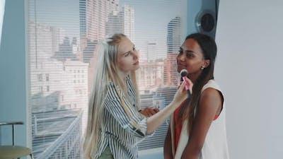 Middle Closeup of Makeup Artist Applying Makeup on Beautiful Mixedrace Model