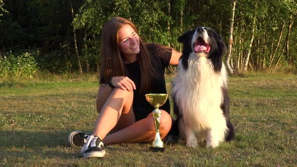 Thumbnail for A Woman and a Border Collie Sit in a Meadow with a Trophy, the Woman Shows the Trophy To the Dog