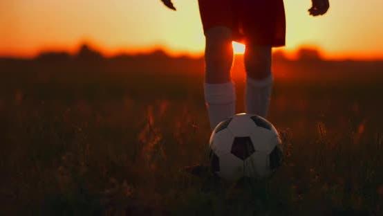 Feet Running with a Soccer Ball Running Across the Field at Sunset