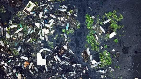 Rubbish accumulated at dark river. Pollution environment.