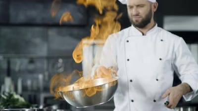 Man Chef Cooking in Pan with Fire in Slow Motion at Kitchen. Young Chef