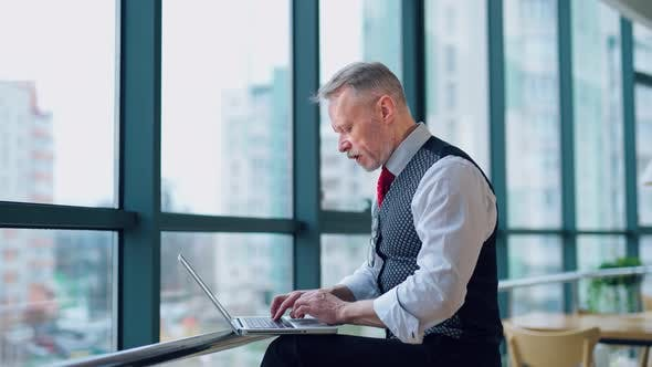 Thumbnail for Thoughtful middle aged businessman in suit with a laptop