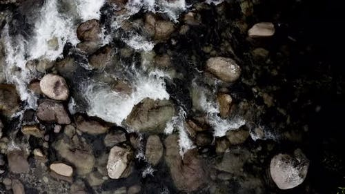 Top view of a waterbed full of rocks in a coloration close to black and white