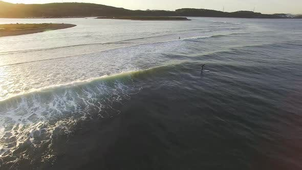 Drone View of Surfers Waiting for a Wave in the Sea at Sunset