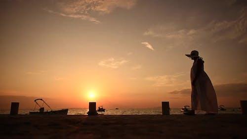 Woman Walking Along the Sea Shore During Sunset