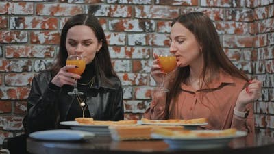 Young Girls Eat in a Cafe and Talk