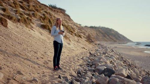 Photographer Using Slr Camera On Beach