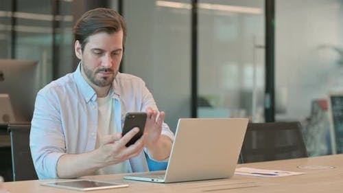 Man with Laptop Using Smartphone